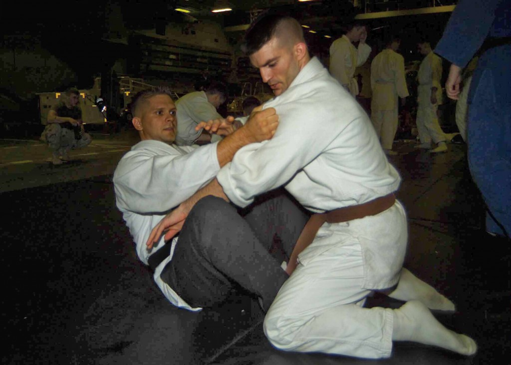 Lance Cpl Aaron Jacobs graples with 1stLt. Steve Gaspar during Judo training held in the hangar bay aboard the USS Nassau.